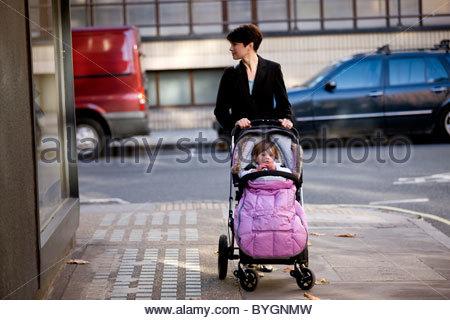 Eine Mutter schob einen Kinderwagen, auf der Suche in einem Schaufenster - Stockfoto