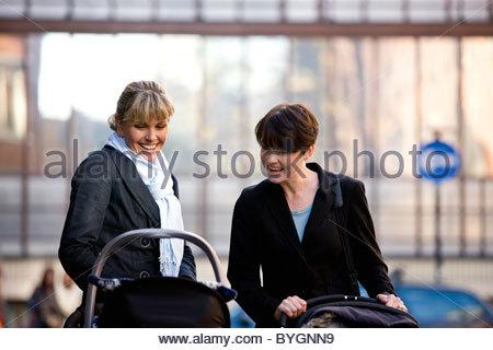 Zwei Mütter schieben ihre Buggys auf der Straße - Stockfoto