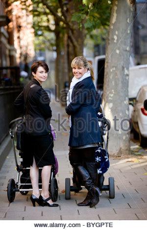 Zwei Mütter mit Kinderwagen auf der Straße stehen lächelnd - Stockfoto