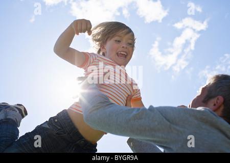 Low-Winkel Ansicht Vater Sohn in hellem Sonnenlicht, hinterleuchtete heben - Stockfoto