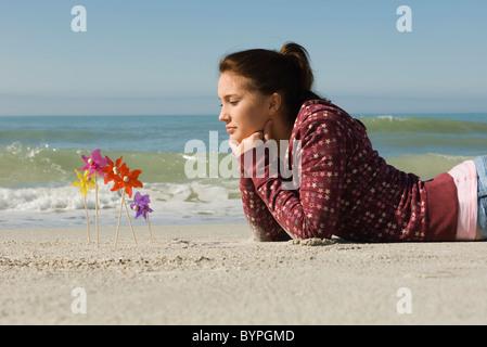 Preteen Mädchen liegend auf Bauch am Strand, nachdenklich betrachtet man Windräder in den Sand stecken - Stockfoto
