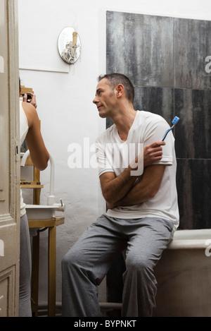 Mann im Badezimmer warten, während Frau Make-up gilt - Stockfoto