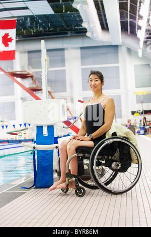 eine Frau in einem Rollstuhl sitzt neben einem Lift am Rande eines Swimmingpools; Edmonton, Alberta, Kanada - Stockfoto