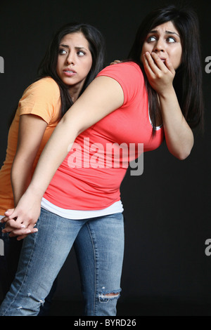 zwei Mädchen dicht zusammengedrängt auf der Suche nach sehr viel Angst - Stockfoto