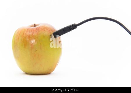 Einen eigentlichen Apfel steckte in ein USB-Kabel auf einem weißen Hintergrund - Stockfoto