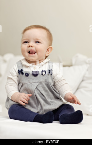 Porträt von hungrigen 6 Monate weibliches Kind sitzt auf dem Bett. Vertikale Form, Vorderansicht, Textfreiraum - Stockfoto