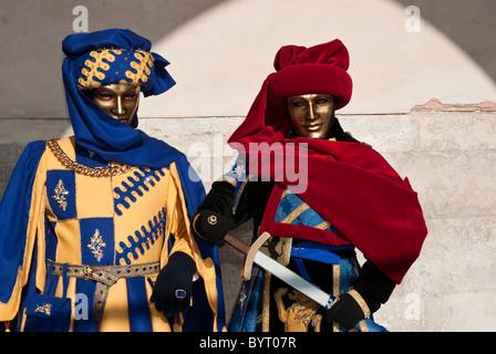 Paar von venezianischen Masken Fasching im Mittelalter zu verschleiern, mit Mantel und Schwert - Stockfoto