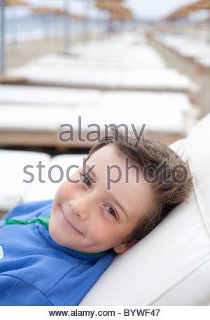 Junge auf der Sonnenliege am Strand liegend - Stockfoto