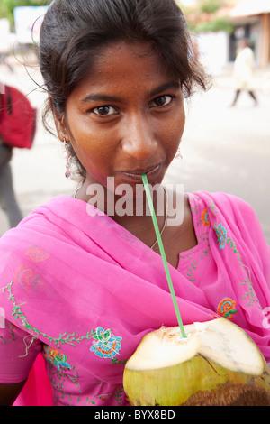 eine junge Frau aus einer Kokosnuss mit dem Strohhalm zu trinken; Mysore, Karnataka, Indien - Stockfoto
