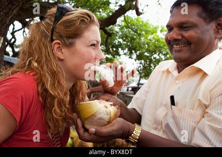 eine Frau, die Essen das Fleisch einer Kokosnuss, wenn ihr von einem Mann angeboten; Mysore, Karnataka, Indien - Stockfoto