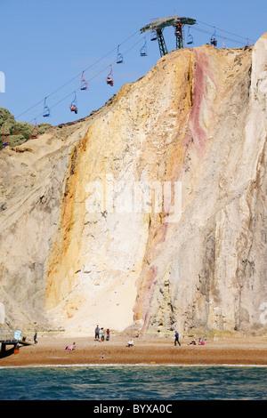 Seilbahnen, die die Menschen nach unten über die bunten Klippen auf den Strand von Alaun-Bucht - Stockfoto