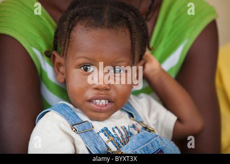 ein junges Mädchen in einem Erwachsenen Armen gehalten; Grand Saline, haiti - Stockfoto
