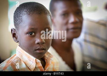 ein Junge sitzt neben seinem Vater; Grand Saline, haiti - Stockfoto