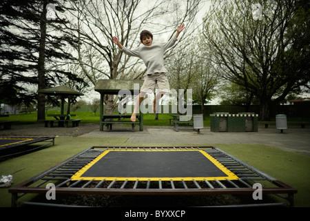 Junge springt auf Trampolin im öffentlichen Spielplatz, Neuseeland. - Stockfoto
