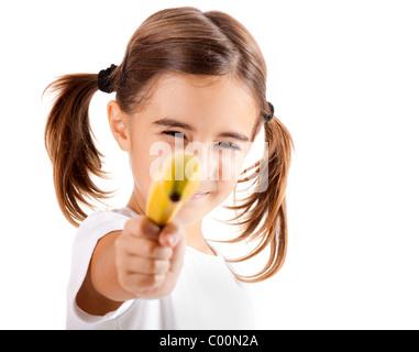 Kleines Mädchen isoliert auf weißem vorgibt ist schießen mit einer Banane - Stockfoto