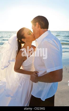 Ehepaar, Braut und Bräutigam küssen bei Sonnenuntergang auf einer wunderschönen tropischen Strandhochzeit - Stockfoto