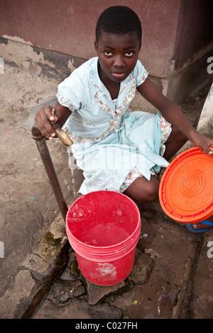 Eine Mädchen füllt einen Eimer am kommunalen Wasserhahn in Dar Es Salaam, Tansania, Ostafrika. - Stockfoto