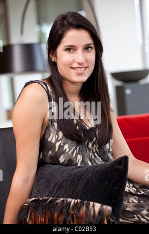 Junge Frau sitzt bequem auf dem Sofa in ihrer Wohnung - Stockfoto