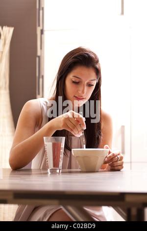Junge Frau sitzt bequem an einem Esstisch, frühstücken - Stockfoto