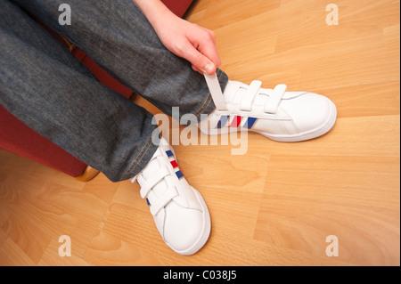 Ein MODEL Release Bild eines elfjährigen Jungen Befestigung Sneaks Klettverschluss im Vereinigten Königreich - Stockfoto