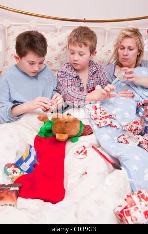 Ein MODEL Release Bild von zwei jungen (11 und 7) und Mama Eröffnung Weihnachten präsentiert im Bett von ihrer Strümpfe - Stockfoto