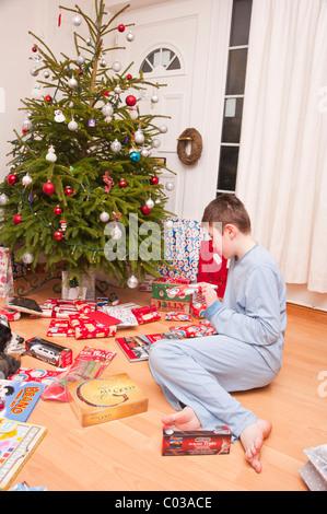 Ein MODEL Release Bild eines elfjährigen Jungen öffnen Weihnachten präsentiert unter dem Baum im Vereinigten Königreich - Stockfoto