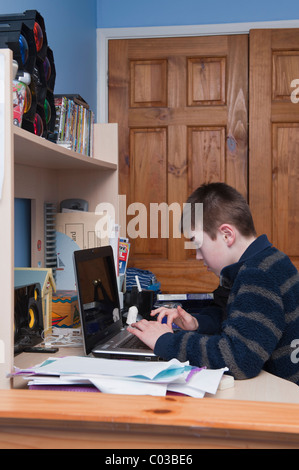 Ein MODEL Release Bild eines elfjährigen Jungen Hausaufgaben auf seinem Laptopcomputer in seinem Schlafzimmer - Stockfoto