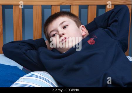 Ein MODEL Release Bild eines elf Jahre alten Jungen vor dem Fernseher in seinem Schlafzimmer im Vereinigten Königreich - Stockfoto