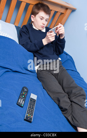 Ein MODEL Release Bild eines elfjährigen Jungen spielen mit seinem Ipod Touch in seinem Schlafzimmer im Vereinigten - Stockfoto