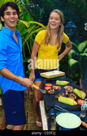 Junge Paare, die haben eines Grillplatz in ihrem Garten in hawaii - Stockfoto