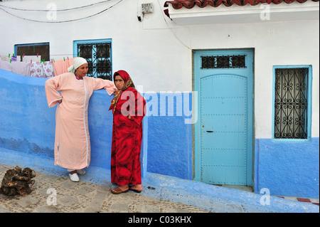 Zwei Frauen tragen traditionelle Kleidung, Djelabba, vor einem Haus in der blauen Stadt Chefchaouen, Rif-Gebirge - Stockfoto