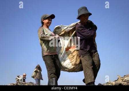 Ein junger Mann und eine Frau tragen eine große Tasche voller Müll auf einer verschmutzten Mülldeponie in Phnom - Stockfoto