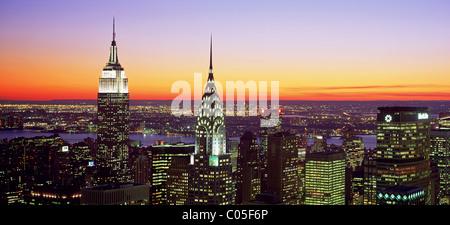 New York City Skyline Blick nach Westen mit dem Empire State Building und Chrysler Building in der Abenddämmerung. - Stockfoto