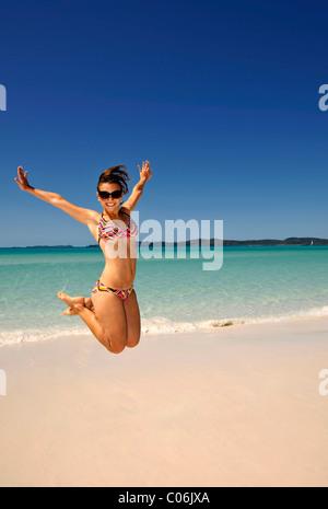 Junge Frau am Meer, in die Luft springen symbolisches Bild Vitalität, Whitehaven Beach, Whitsunday Island - Stockfoto