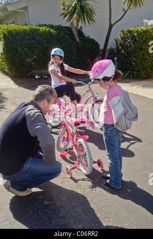 Papa hilft seine fünfjährige Tochter lernen, ihr neues Fahrrad fahren, mit neun Jahre alte Schwester in Laguna Niguel, - Stockfoto