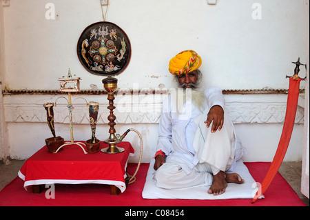 Alten indischen Mann in traditioneller Kleidung mit Turban und Wasserpfeife, Meherangarh Fort, Jodhpur, Rajasthan, - Stockfoto
