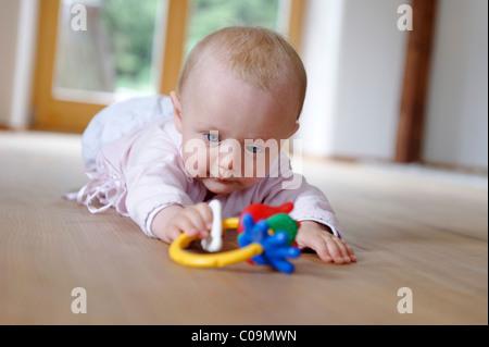 Kleines Baby, 4 Monate, liegend auf dem Bauch, mit Beißring - Stockfoto