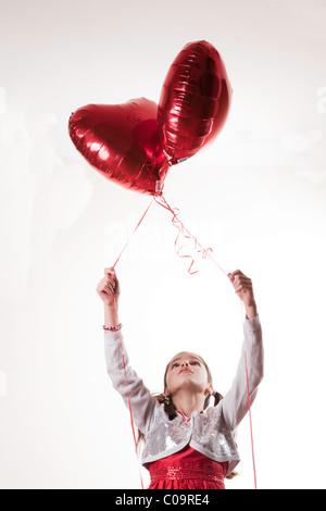 glückliches Mädchen hält einen Ballon in Herzform - Stockfoto