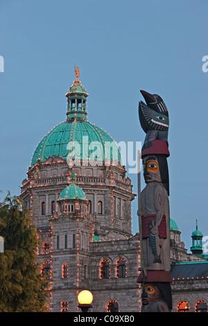 Erste Nationen Totempfahl vor dem beleuchteten BC Parlamentsgebäude im Innenhafen in der Stadt Victoria, Vanco