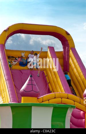 Kinder spielen am aufblasbaren Rutsche und Hüpfburg - Stockfoto