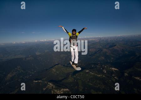 Mann an Bord der Himmel fliegt über die Berge in den blauen Himmel. - Stockfoto