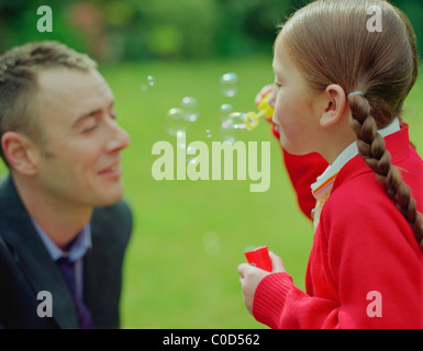 Vater und Tochter Seifenblasen im Garten - Stockfoto