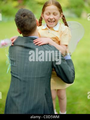 Vater Holding Tochter Feenflügel tragen - Stockfoto