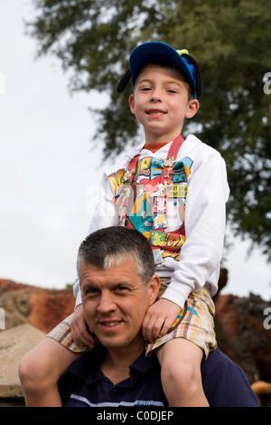 Ein Junge sitzt auf seines Vaters Schultern und zeigt stolz seine Disney Handel Stifte, ein beliebtes sammeln Element - Stockfoto