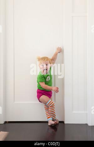 Kleines Mädchen, die versuchen, in verschlossenen Tür - Stockfoto