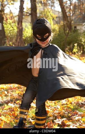 Kid verkleidet wie Batman spielen in den Blättern - Stockfoto