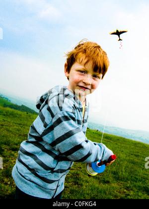 Kleiner Junge auf einem Hügel im Süden Wales UK läuft im Wind und ein Drachen - Stockfoto