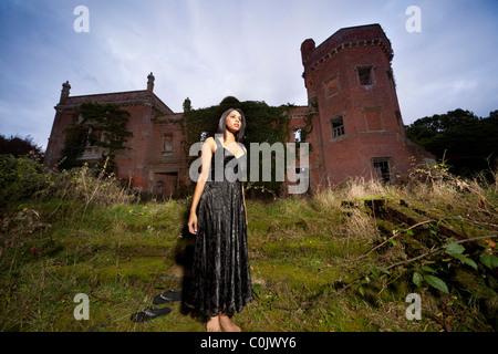 mysteriöse Frau stand vor einer alten verfallenen großes Land Herrenhaus - Stockfoto