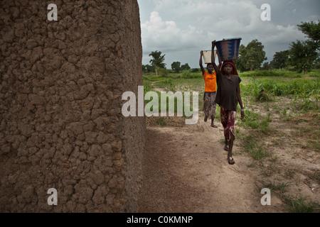 Mädchen bringen Sie nach Hause Wasser aus einem Brunnen in Safo, Mali, Westafrika. - Stockfoto