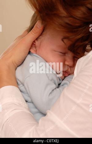 Mutter Kuscheln ein schlafendes Baby in ihren Armen - Stockfoto